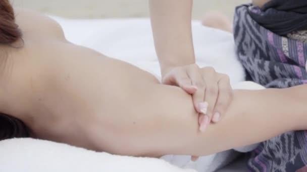 Schöne glückliche junge asiatische Frau sexy Thai-Massage auf den Armen mit Masseurin am Strand tropischen zusammen, Mädchen entspannen und ruhen im Urlaub Körpermassage mit Öl auf dem Meer mit Behandlung im Sommer.
