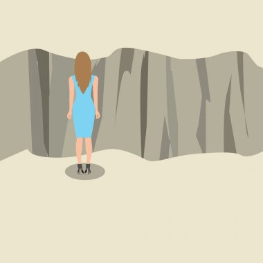 Young woman standing and looking at the edge of a cliff.