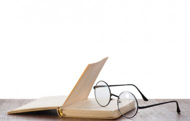 Eyeglasses and book on table