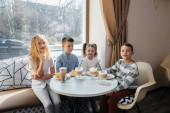 Velká přátelská společnost dětí slaví dovolenou v kavárně s lahodným dezertem. V den narození