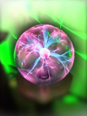 Hand touching a plasma ball with smooth magenta-blue flames