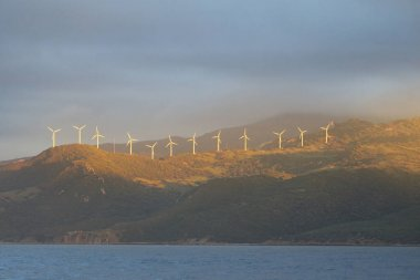 Wind turbines at the Rock of Gibraltar at sunrise, a view from the yacht. British Overseas Territory. Epic cloudscape. Alternative energy, power generation, environmental damage and conservation