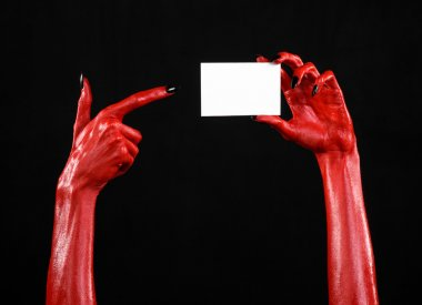 Halloween theme: Red devil hand with black nails holding a blank white card on a black background