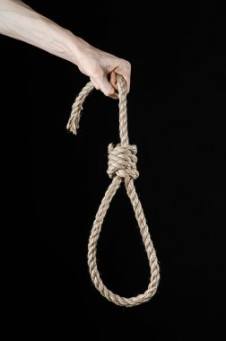 Lynching and suicide theme: man's hand holding a loop of rope for hanging on black isolated background