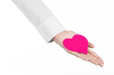 Heart Disease and Health Topic: hand doctor in a white shirt holding a card in the form of a pink heart isolated on a white background in studio