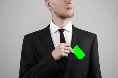 businessman in a black suit and black tie holding a card, a hand holding a card, green card, card is inserted, the green chroma key card, gray background, isolated, business theme, theme of banking