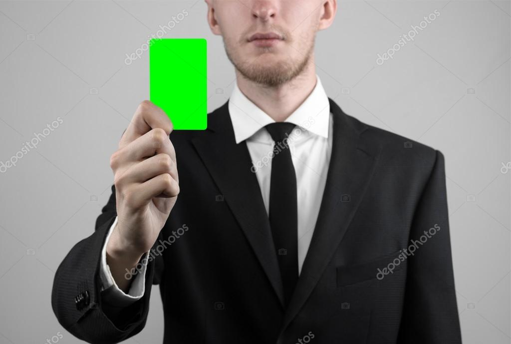 businessman in a black suit and black tie holding a card a hand