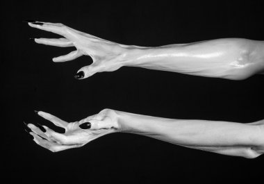 white hands of death with black nails, white death, the devil's hands, the hands of a demon, white skin, halloween theme, black background, isolated
