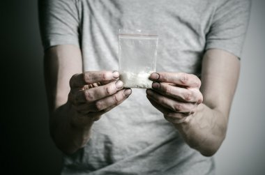 The fight against drugs and drug addiction topic: addict holding package of cocaine in a gray T-shirt on a dark background in the studio