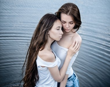 Dramatic portrait of a girl portrait of two beautiful girls on a background of water
