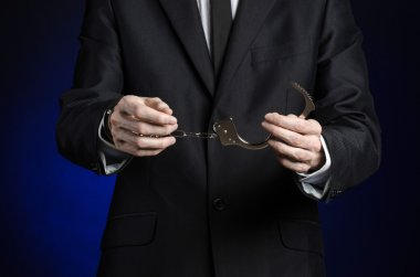 Corruption and bribery theme: businessman in a black suit with handcuffs on his hands on a dark blue background in studio isolated
