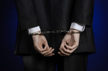 Corruption and bribery theme: businessman in a black suit with handcuffs on his hands on a dark blue background in studio isolated view from the back
