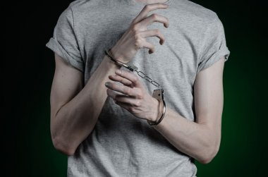 Prison and convicted topic: man with handcuffs on his hands in a gray T-shirt and blue jeans on a dark green background in the studio, put handcuffs on the drug dealer