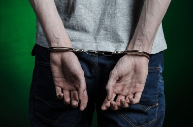 Prison and convicted topic: man with handcuffs on his hands in a gray T-shirt and blue jeans on a dark green background in the studio, put handcuffs on the drug dealer, the view from the back