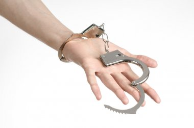 Prison and convicted topic: man hands with handcuffs isolated on white background in studio, put handcuffs on killer