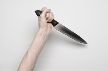 Murder and Halloween theme: A man's hand reaching for a knife, a human hand holding a knife isolated on a gray background in studio from above