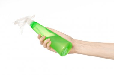 Cleaning the house and cleaner theme: man's hand holding a green spray bottle for cleaning isolated on a white background