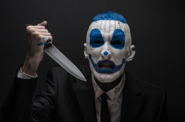 Terrible clown and Halloween theme: Crazy blue clown in a black suit with a knife in his hand isolated on a dark background in the studio