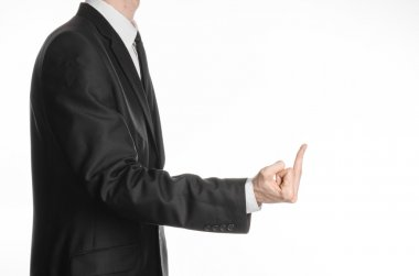 Businessman and gesture topic: a man in a black suit showing middle finger on an isolated white background in studio