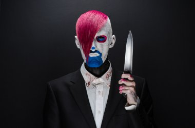 Clown and Halloween theme: Scary clown with pink hair in a black suit with a knife in his hand on a dark background in the studio
