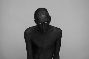 Gothic and Halloween theme: a man with black skin is isolated on a gray background in the studio, the Black Death body art