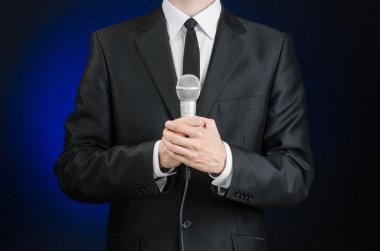 Business and speech topic: Man in black suit holding a microphone on a gray dark blue isolated background in studio