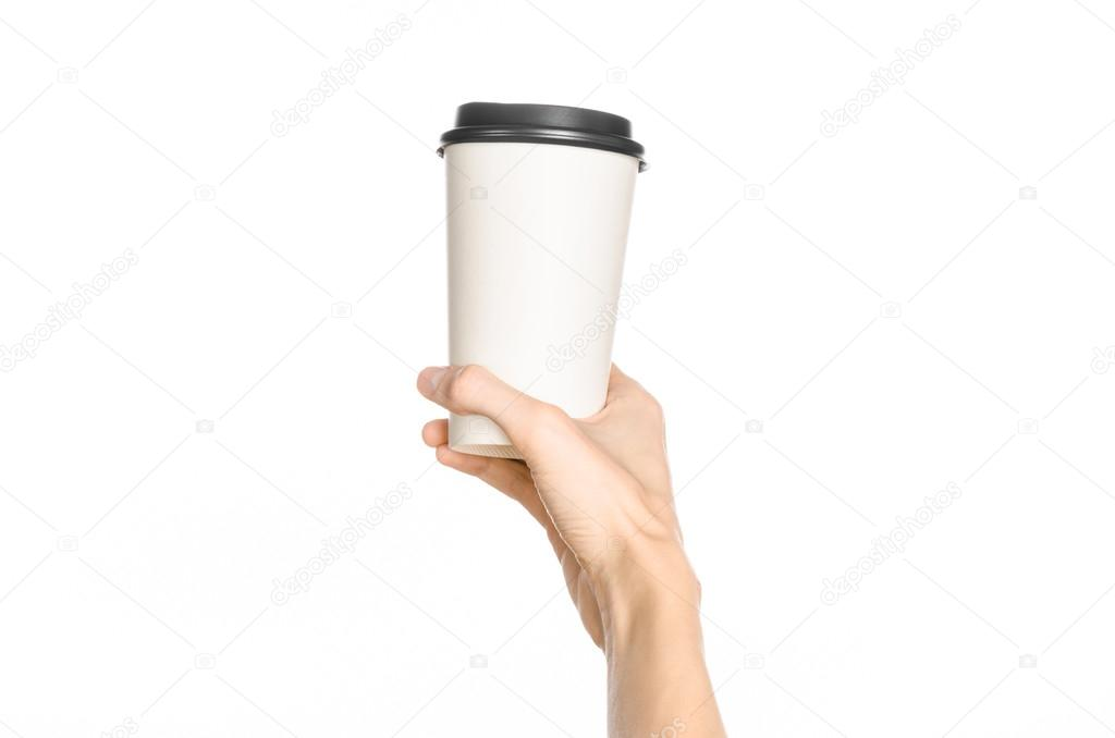 Breakfast and coffee theme: man's hand holding white empty paper coffee cup with a brown plastic cap isolated on a white background in the studio, advertising of coffee first-person view