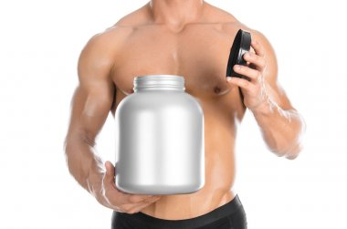 Bodybuilding and Sports theme: handsome strong bodybuilder holding a plastic jar with a dry protein and showing gesture isolated on white background in studio