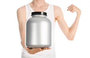 Bodybuilding and Sports theme: a thin man in a white T-shirt and jeans holding a plastic jar with a protein isolated on a white background in studio