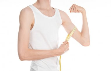 Bodybuilding and Sports theme: a thin man in a white T-shirt and jeans with measuring tape isolated on a white background in studio