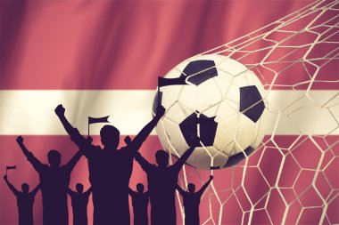 silhouettes of Soccer fans with flag of Latvia .Cheer Concept vi