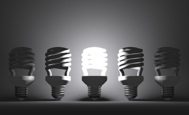 Glowing spiral Light bulb among dead ones on gray
