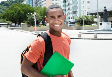 Laughing african american male student in city