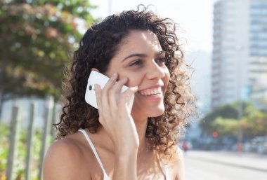 Latin woman in the city speaking at phone