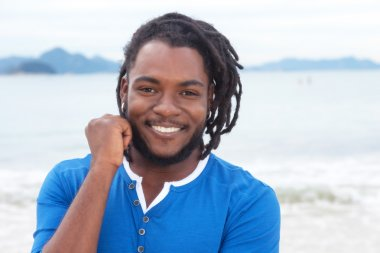 Laughing african american guy with dreadlocks at beach