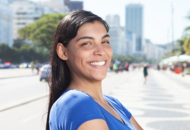 Happy latin woman with long dark hair in the city