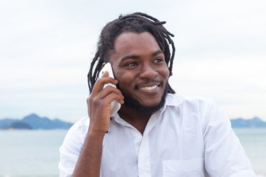 African american guy with dreadlocks and white shirt at phone
