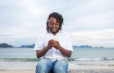 African american guy with dreadlocks and white shirt typing mess