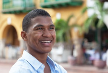 Dreaming guy in a blue shirt in a colorful colonial town