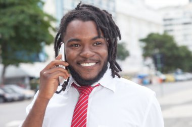 African american businessman with dreadlocks at phone in the cit