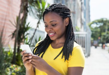 African american woman in a yellow shirt texting message with mo