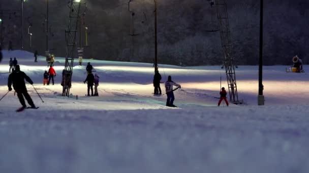 Skiers using Ski lift on winter evening, night skiing