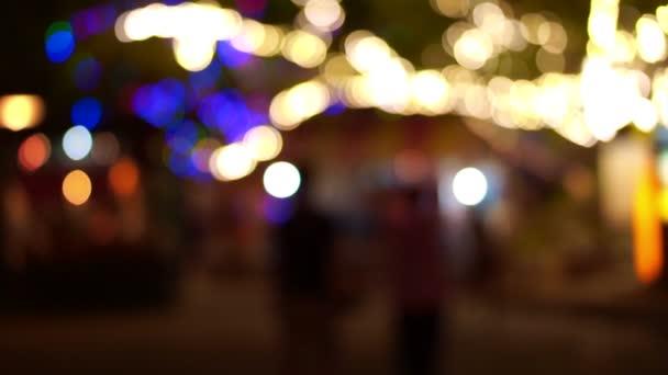 A nagy fák és az emberek sziluettje színes lámpák fesztivál alatt sétálva világítás homályos