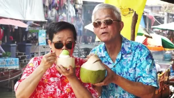 HD video of Asian senior couple travel to thailand floating market. Drinking fresh coconut juice