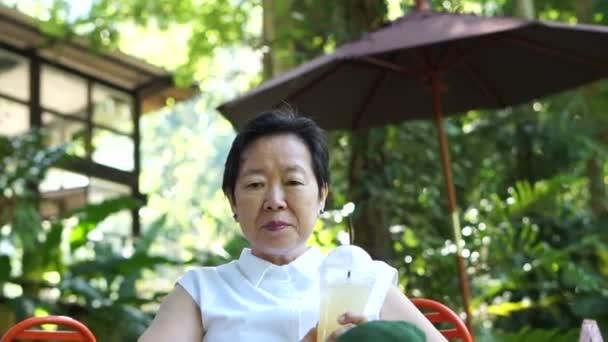 Asijské starší žena šťastně pití kávy v kavárně zelené svěží přírody