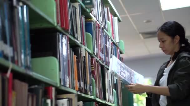 Žena, Asiatka studentské stojan hledání knihovny, knihy