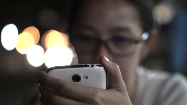 Černé a bílé prosklené asijské ženy SMS pomocí smartphonu s městem v noci světlé pozadí
