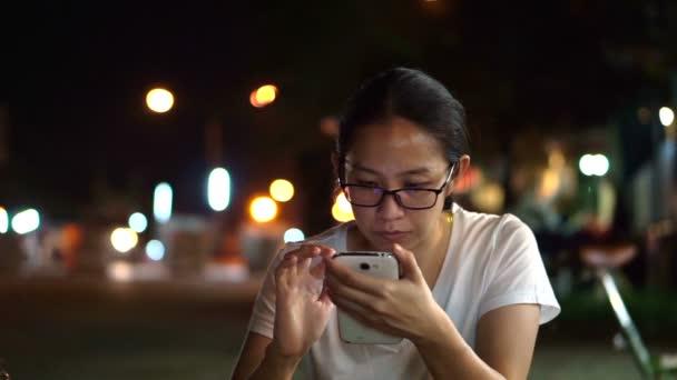 Zasklené asijské ženy SMS pomocí smartphonu s městem v noci světlé pozadí