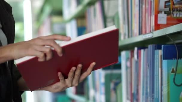 Ázsiai lány keres könyv, flip, és tegye vissza a könyvtár polcain