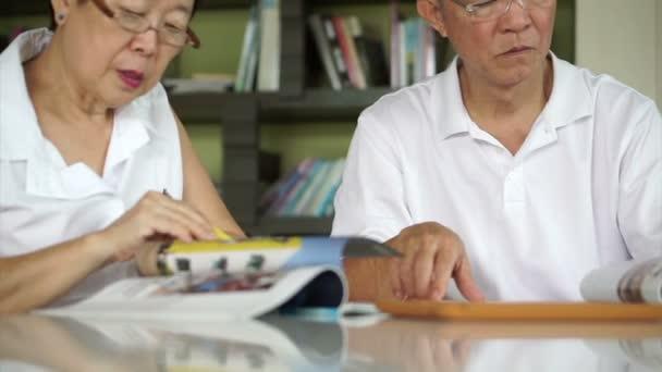 Asijské starší pár, čtení knih a časopisů dohromady v malé knihovny. Koncepce vzdělávání a studium